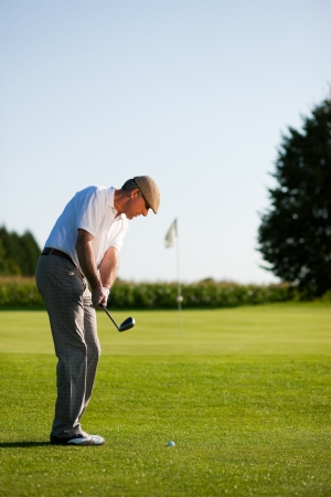 Senior golfer doing a golf stroke, he is playing on a wonderful summer afternoon Stock Photo - 14125539