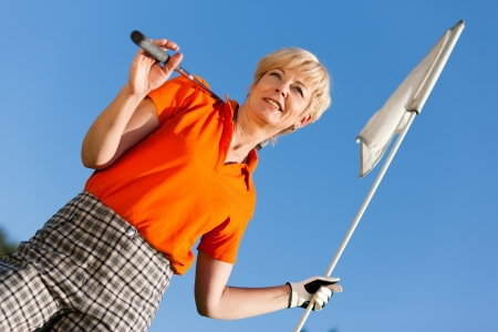 Senior woman playing golf holding the flag in her hand photo