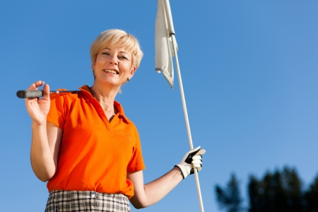 Senior woman playing golf holding the flag in her hand Stock Photo - 14124535