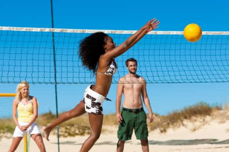 Group of friends - here two women and a man - playing beach volleyball, one in front having the ball photo