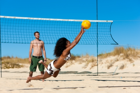 beach front: Group of friends – here two women and a man - playing beach volleyball, one in front having the ball