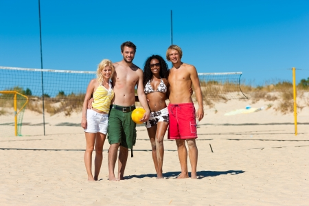 Group of friends - women and men - playing beach volleyball, they having a break and lying in the sun photo