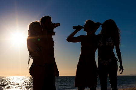 People (two couples) on the beach having a party, drinking and having a lot of fun in the sunset (only silhouette of people to be seen, people having bottles in their hands with the sun shining through) photo