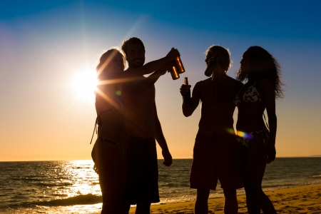 guy on beach: People (two couples) on the beach having a party, drinking and having a lot of fun in the sunset (only silhouette of people to be seen, people having bottles in their hands with the sun shining through)