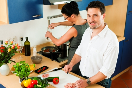 cutting vegetables: Young couple - man and woman - cooking in their kitchen at home preparing vegetables for salad and pasta sauce