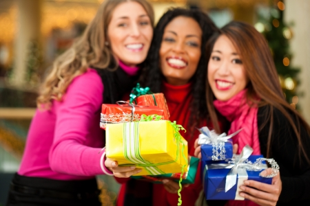 Group of three women - white, black and Asian - with Christmas presents in a shopping mall in front of a Christmas tree photo