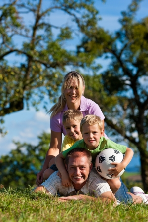 Family with two little boys playing in the grass on a summer meadow - they have a football photo