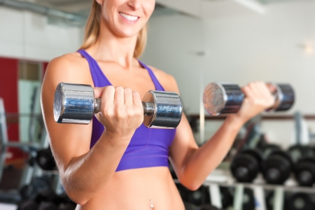 pectoral: Young woman is exercising with barbell in gym to strengthen the muscles