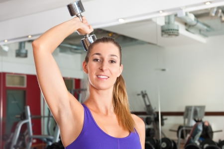 triceps: Young woman is exercising with barbell in gym to strengthen the muscles