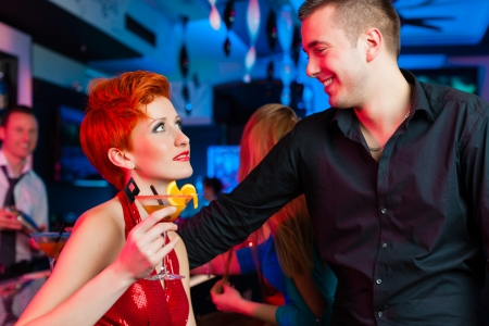 woman bar: young couple in bar or club drinking cocktails