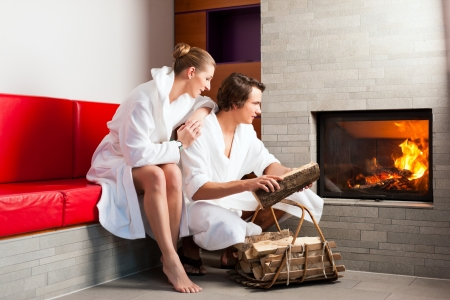 woman bathrobe: Young couple sitting in bathrobe for open fireplace, it is very romantic