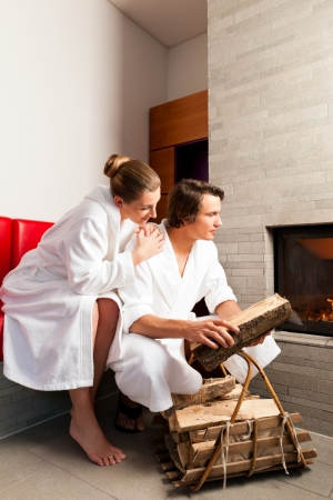 Young couple sitting in bathrobe for open fireplace, it is very romantic photo