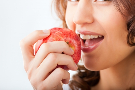 Healthy nutrition and healthy teeth or diet, young woman bites in a apple photo