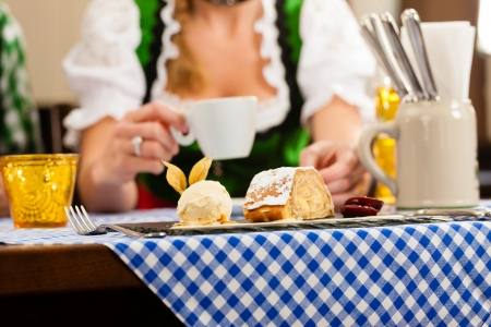 Young woman in traditional Bavarian Tracht in restaurant or pub eating dessert, close-up  Stock Photo - 14041038
