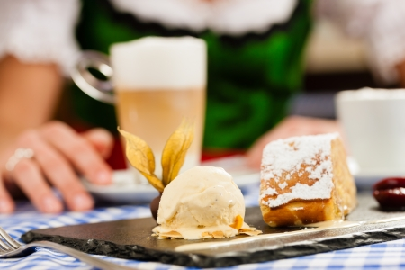 Young woman in traditional Bavarian Tracht in restaurant or pub eating dessert and drinking coffee, close-up  photo
