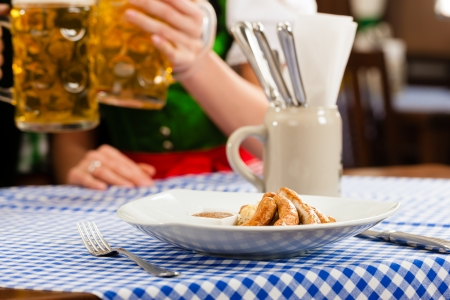 Young woman in traditional clothes - dirndl - eating sausage in restaurant or pub, close-up Stock Photo - 14041005