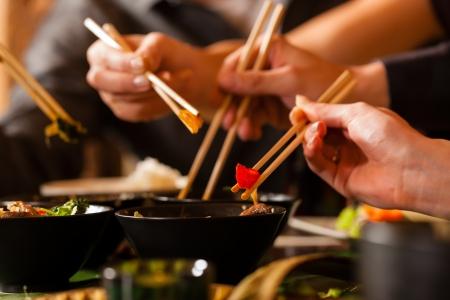Los jóvenes que comen en un restaurante tailandés, que comer con palillos, primer plano en las manos y los alimentos Foto de archivo