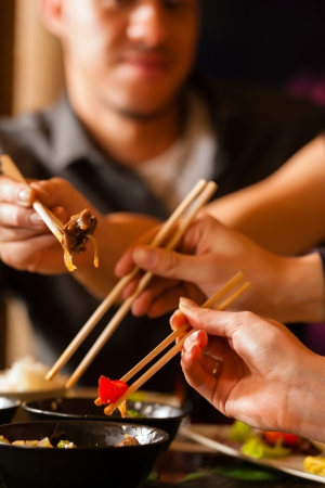 chopstick: Young people eating in a Thai restaurant, they eating with chopsticks