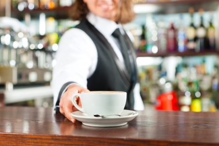 Barista making cappuccino in his coffeeshop or cafe photo