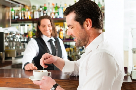 serve: Coffeeshop - barista in cafe with a client, he is drinking coffee