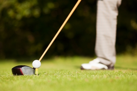 Golfer only feet to be seen - doing a golf stroke, he is playing on a wonderful summer afternoon Stock Photo - 14124169