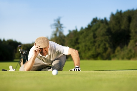 Senior man playing golf aiming for the hole, it is a wonderful clear summer late afternoon, the colors are very vivid Stock Photo - 14095509