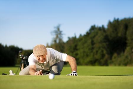 mature adult men: Uomo anziano, giocare a golf puntando il buco, � un bel pomeriggio d'estate chiaramente alla fine, i colori sono molto vividi