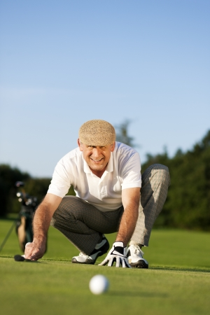 Senior man playing golf aiming for the hole, it is a wonderful clear summer late afternoon, the colors are very vivid Stock Photo - 14095511