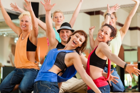 Zumba or Jazzdance - young people dancing in a studio or gym doing sports or practicing a dance number Stock Photo