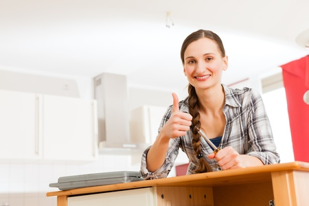 thumps up: Young woman is assembling a cupboard because she is moving in or out - thumps up