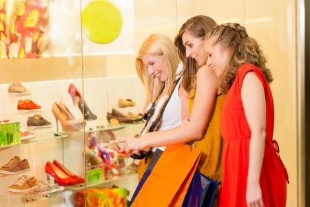 Friends shoe shopping in a mall or shop having fun photo