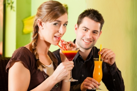 Young happy couple drinking cocktails in bar or restaurant; presumably it is a first date photo