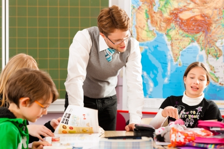 tuition: Education - Pupils and teacher learning at elementary or primary school in the classroom Stock Photo