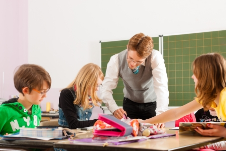 Education - Pupils and teacher learning at elementary or primary school in the classroom Stock Photo - 14725146