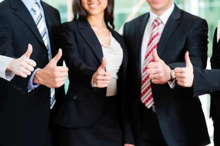 team spirit: Business - group of businesspeople posing for group photo in office showing thumbs up Stock Photo