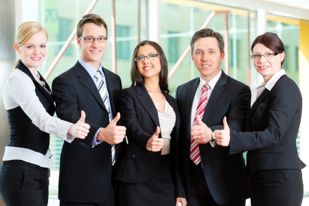 group photo: Business - group of businesspeople posing for group photo in office showing thumbs up Stock Photo