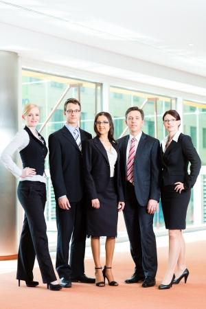 Business - groupe de gens d'affaires posant pour la photo de groupe dans le bureau montrant thumbs up
