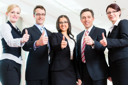 employees working: Business - group of businesspeople posing for group photo in office showing thumbs up Stock Photo