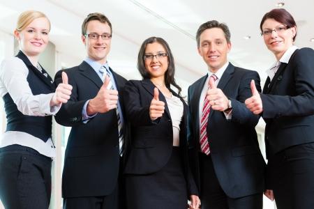 Business - groep van ondernemers poseren voor groepsfoto in het kantoor zien thumbs up