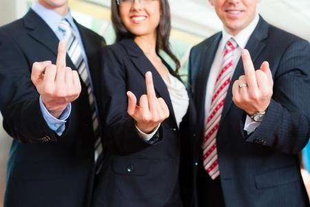 mittelfinger: Business - Gruppe von Gesch�ftsleuten posieren f�r Gruppenfotos in B�ro zeigt mit dem Finger