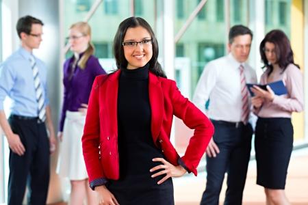 Les gens d'affaires ou de l'équipe dans le bureau, une femme cherche à le spectateur Banque d'images