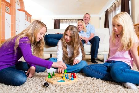 jeune fille adolescente: Famille jouant jeu de plateau ludo � l'aise sur le plancher