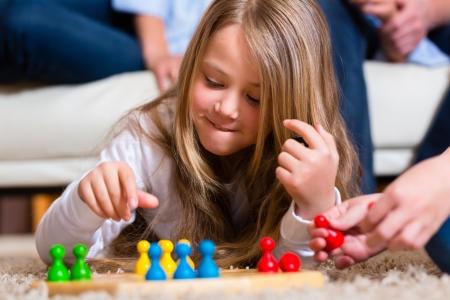 brettspiel: Familie spielt Brettspiel Ludo zu Hause auf dem Fu�boden, Nahaufnahme auf Kind