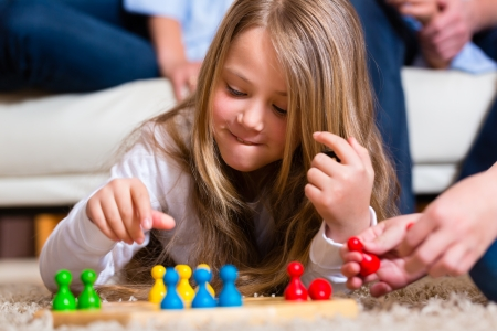 board game: Family playing board game ludo at home on the floor, close up on child Stock Photo