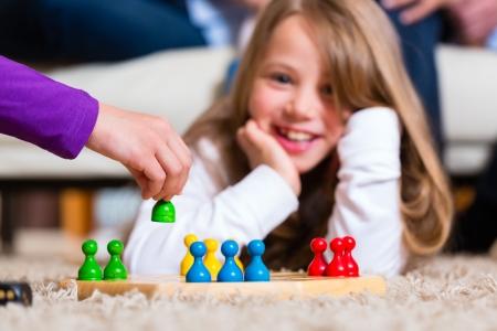 brettspiel: Familie spielt Brettspiel Mensch �rgere dich zu Hause auf dem Boden, auf dem Arm vor konzentrieren Lizenzfreie Bilder