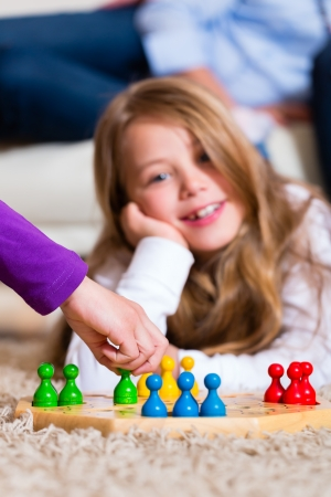 kids games: Family playing board game ludo at home on the floor, focus on the arm in front