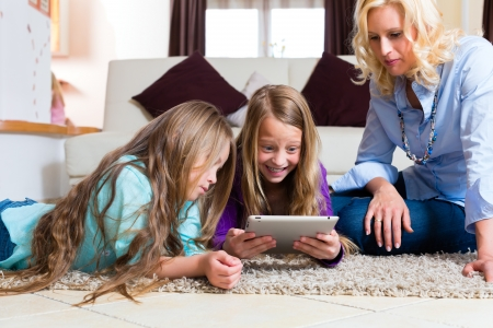 Family - mother and two daughters - playing with tablet computer lying on the floor at home photo