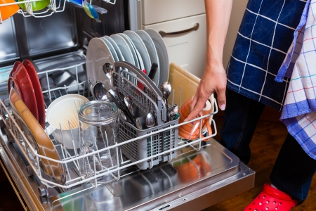 cropped image: Housewife is doing the dishes with dishwasher, cropped image
