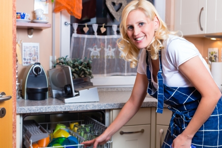dishwasher: Young housewife is doing the dishes with dishwasher
