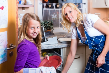 domestic chore: Young housewife is doing the dishes with dishwasher, her daughter is helping her